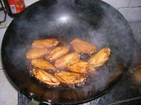 油锅烧热后倒入腌制好的鸡翅,将鸡翅翻炒至金黄色,倒入关键材料——可乐,没过鸡翅为宜