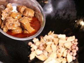 热过入油,小火爆香辅料,加入冬笋和猪蹄、花生翻炒5分钟。