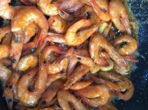 倒入炸好的明虾。倒入生抽,料酒,蚝油和少许的盐,翻炒均匀