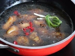 锅中加热水没过猪蹄,最好多加一点开水。葱打结,葱姜蒜、八角、辣椒一起放入