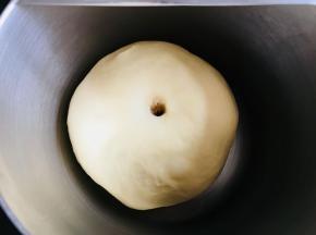 面团稍微按扁于容器中。覆盖保鲜膜发酵至两倍大。