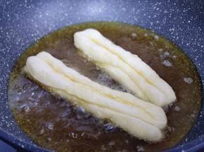 锅中加入食用油,待油温7.8成热时,将油条胚放入油锅中 (有些人总问如何判断油温!很简单,可以用一小块面测试,面团放入锅中,立刻漂浮上来,油温即可)
