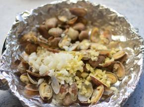 锅中垫一张锡纸,把煮好的花甲、姜、蒜,放在进去