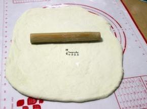 把发酵好的面团,挤出面团内的空气,揉搓成光滑面团,用擀面杖擀成长方形(长椭圆形也可以),擀面的时候,要尽可能把面团里的气泡擀出来。