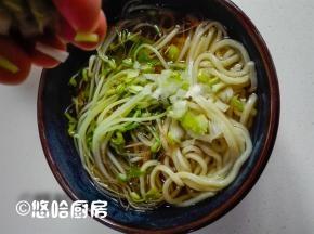 豆芽捞在面条上,浇上适量的面条汤,面条上撒点葱花。