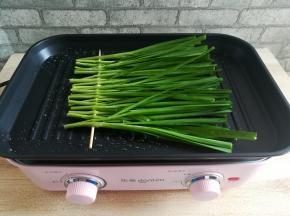 加热东菱多功能锅,烤盘里刷适量的油,放入一串韭菜,转大火用锅铲稍微压一下韭菜,让其均匀受热