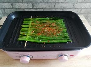 在烤好的韭菜上撒适量的孜然粉,盐和辣椒粉