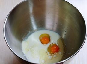 首先将养乐多倒入厨师机桶中,再加入玉米油,草鸡蛋,奶粉,盐和糖对角放。
