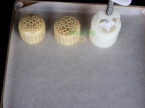 月饼模具内侧撒一些炒熟的糯米粉,防止粘再月饼模具上,然后把做好的月饼面团放入月饼模具里压出月饼形状。