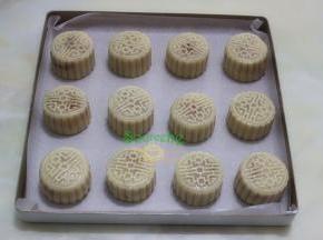 把做的月饼均匀放在烤盘上,并用碰水的瓶子拿在远处轻轻喷一层水。为了月饼颜色好看的,可以再月饼表面涂层鸡蛋液。