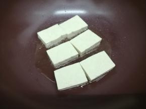 锅里加入适量的油,烧到七成热时,把豆腐摆在锅中