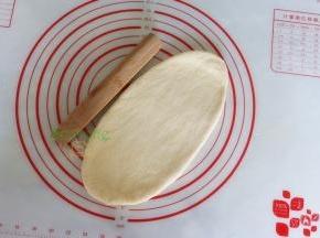 取一个中间发酵好的面团,用擀面杖擀成长椭圆形;