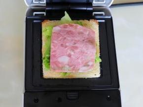 三明治机涂抹一层油,放一片吐司,接着放生菜、沙拉、火腿、再盖上一片吐司,合上机器,时间设置3分钟。