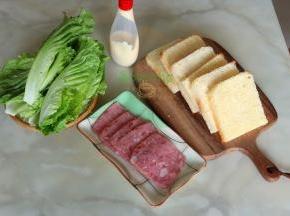 吐司放凉之后切片(最好隔夜切,这个吐司太松软好吃了。),去吐司边,火腿切片,生菜洗净,准备做三明治了。