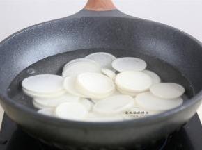 接着先来处理一下白萝卜,烧开一锅清水,把萝卜片放入锅里煮沸,大约4分钟左右,白萝卜变得稍透明,拿起一块,能弯曲即可出锅,千万不要煮烂了。