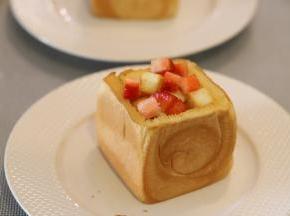草莓洗净切小块,和放凉的吐司块一起放入大的吐司内。
