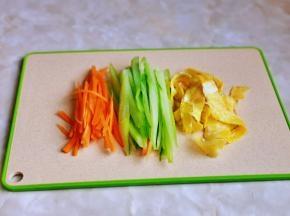 准备备菜,黄瓜去皮切丝,胡萝卜去皮切丝,鸡蛋煎熟后切条。