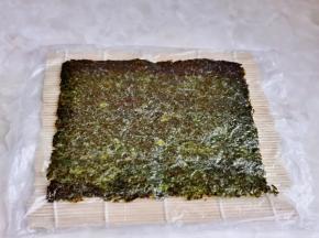 准备寿司卷席,铺上一张保鲜膜,再放上一张海苔。