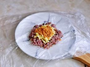 放上马苏里拉芝士,肉松,拿起保鲜膜将饭包起来。