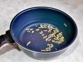 锅中加入一小碗纯净水,再加入腌制好的虾米。
