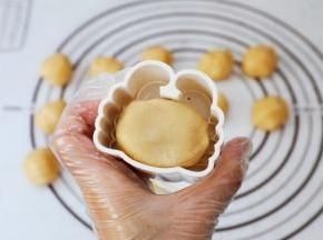 表面撒上适量的手粉,再放入月饼模具中按实