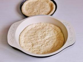 用擀面杖擀成圆饼,放入盘中,用叉子扎出不规则小孔。