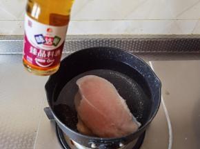 干净不粘锅中倒入半锅清水,放入鸡胸肉片,淋3勺料酒去腥,大火煮开后将鸡胸肉煮熟。
