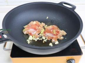锅烧热,倒入少许油,放大蒜煸炒香,放入鸡腿肉,鸡皮朝下。