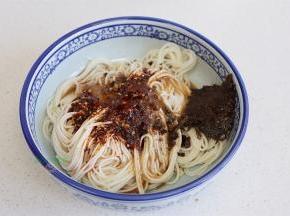 把干香风味肉酱、芽菜、辣油调味料、骨汤。全部倒入面条的碗里,搅拌均匀。盐焗黄豆粒要到热水之后放,可以保持黄豆的酥脆,如果想吃软香的黄豆,可以先放黄豆,再倒沸水。