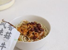把香菇牛肉酱、调味汁、辣椒油、腌萝卜、酸豆角,所有配菜,倒入面条的碗里,搅拌均匀